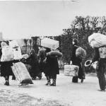 Schwarzweißfoto von Menschen mit schwerem Gepäck