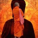 Mönch in orange vor Buddha-Darstellung